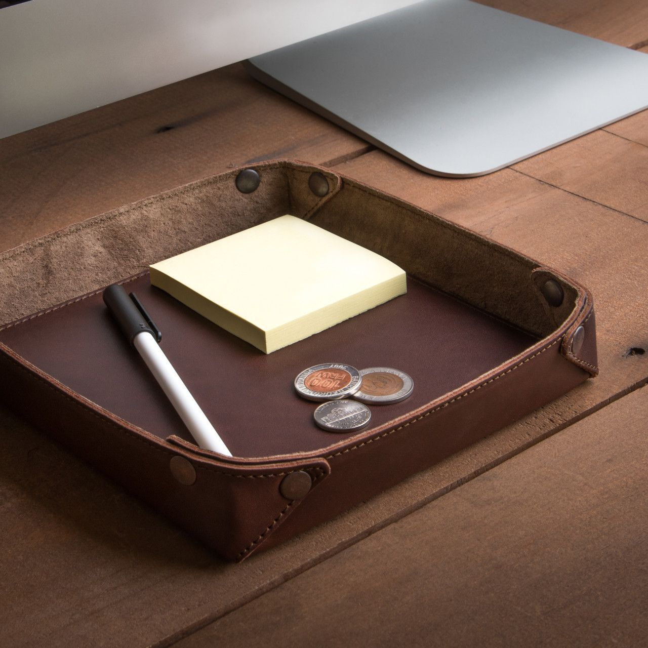 In the inside of the leather valet tray in chestnut leather we can see a pen, notebook and money