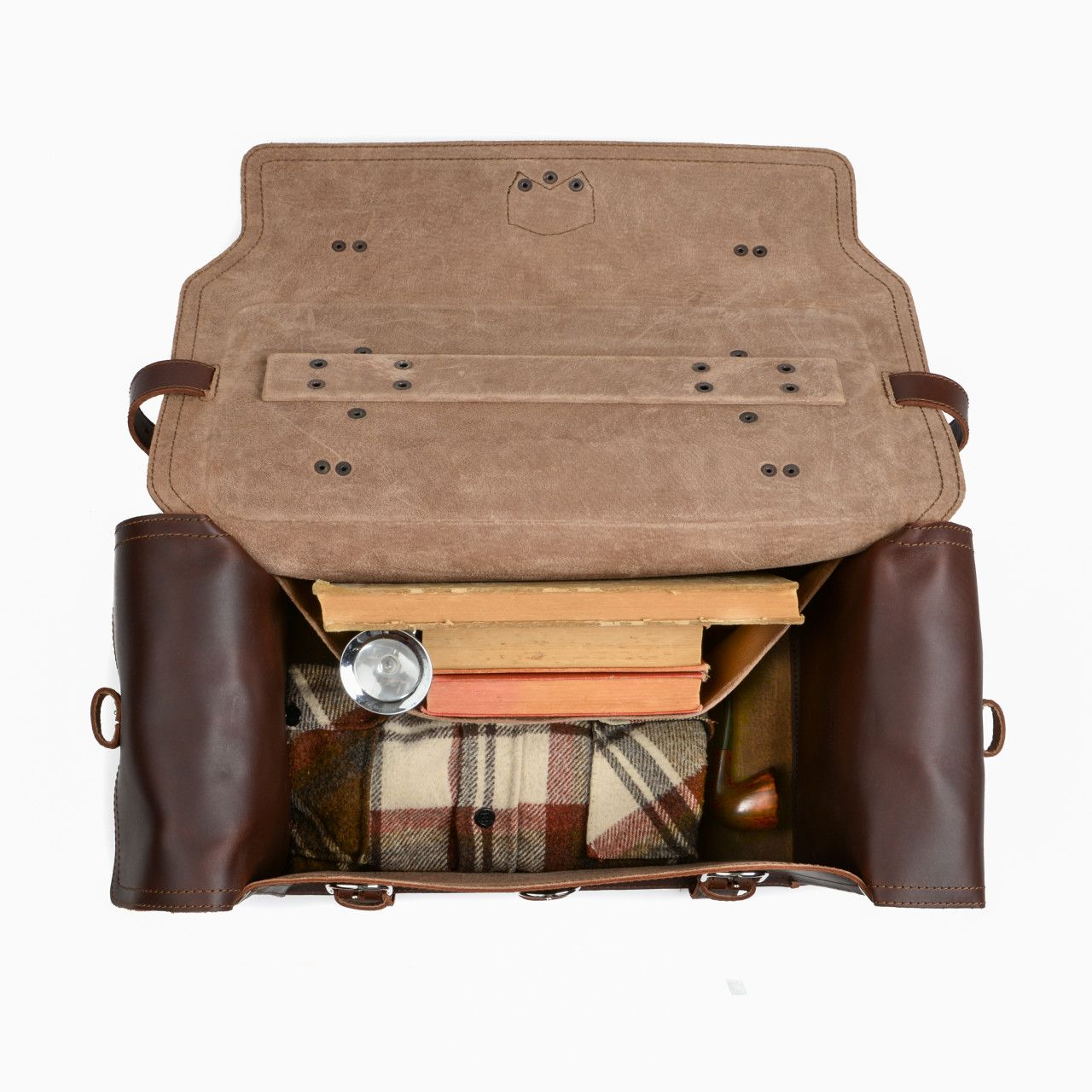 side pocket leather duffel bag large in chestnut leather with books, a shirt, a lashlight and a pipe in the interior