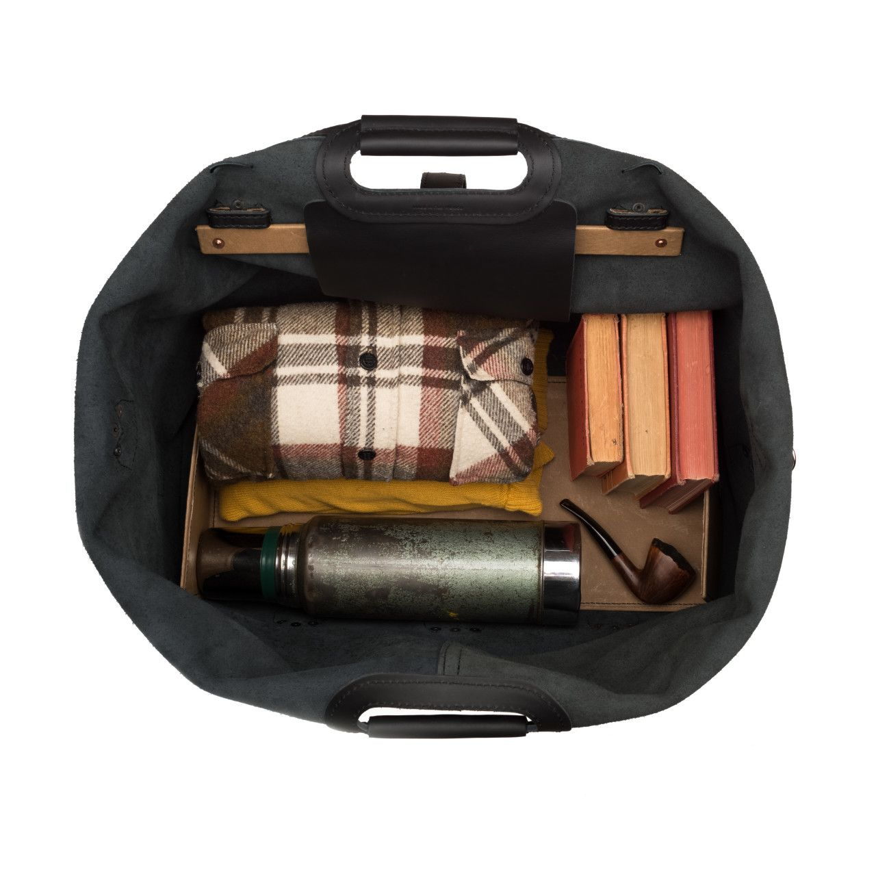 inside the waterbag premium leather duffel bag medium in black leather are shirts, shoes, books, thermo and pipe