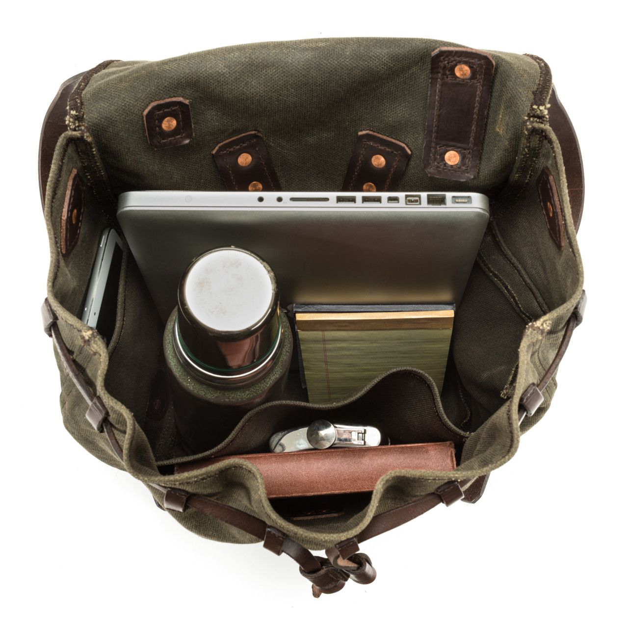 waxed canvas backpack small medium in moss green canvas with a macbook, notebook, thermos in the interior