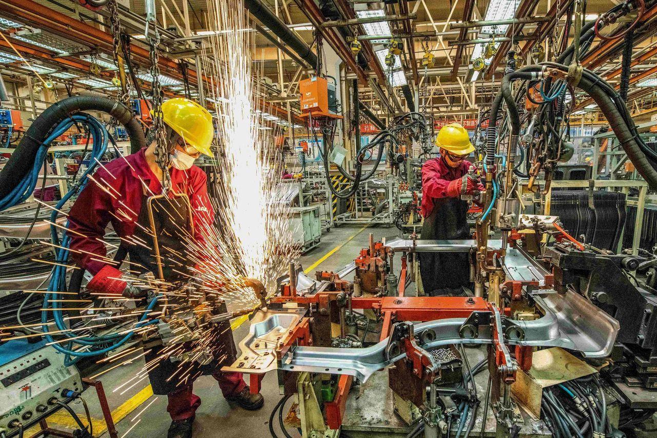 去年6月,山东潍坊一家工厂内,电焊工人在焊接汽车零部件。