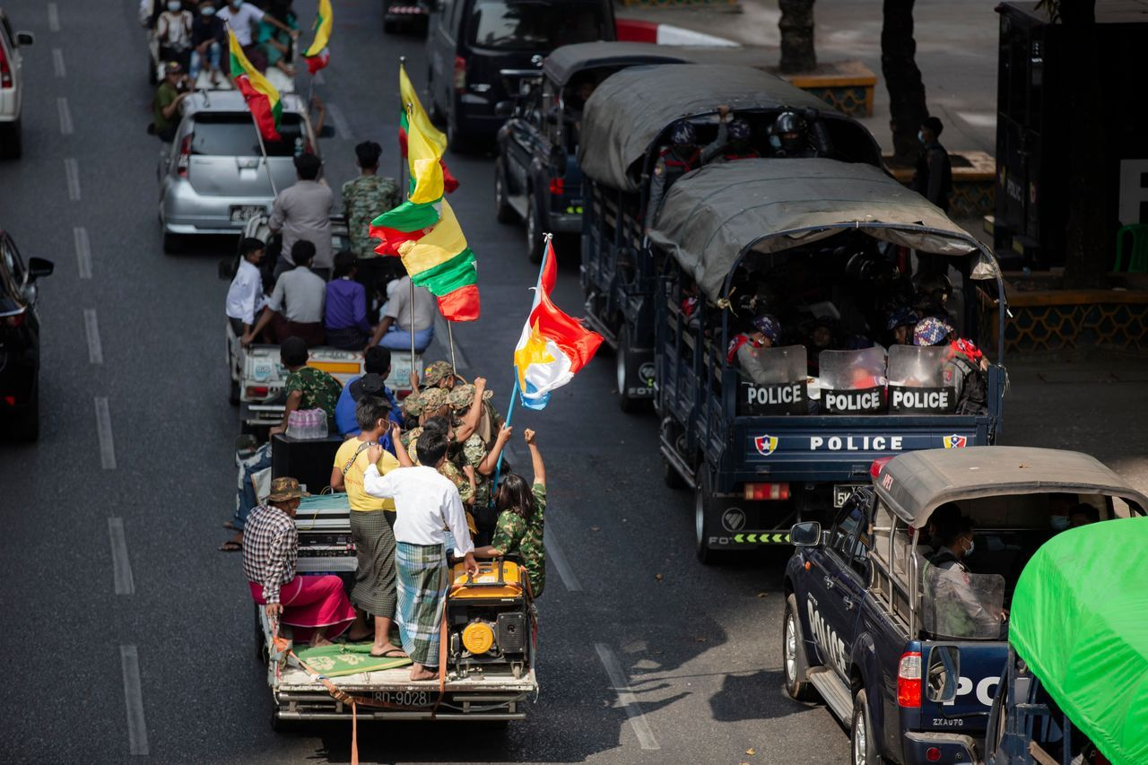 军方支持者在仰光开车经过警车。
