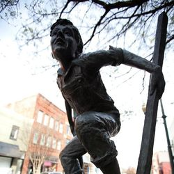 photo of sculpture of child on stilts in downtown Asheville along the Asheville Urban Trail