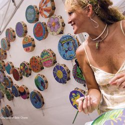 photo of local artist sitting in front of wall of painted tambourines