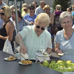 Photo of festival goers putting icing on a fried apple
