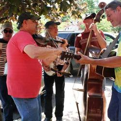 Photo of Men Gathered in Saluda Playing the Violin, the Cello, the Banjo and the Accordion