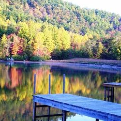 A Photo of A Dock Going into a Lake that Reflects the Fall Colors