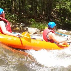 A Photo of People White Water Rafting Down the River