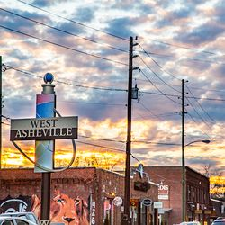 sunset photo of Haywood Road storefronts in West Asheville NC