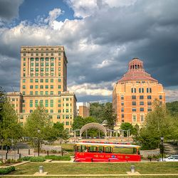 photo of Asheville's historic trolley driving through Pack Square in front of the iconic city and county buildings