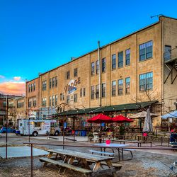photo of backside of Wedge Studios in Asheville's River Arts District, where Wedge Brewery customers sit at picnic tables outside