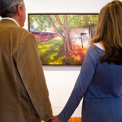 photo of couple holding hands in front of framed photo hanging in local gallery