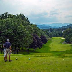Photo of Golfers teeing off with a view of the Blue Ridge Mountains