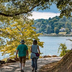 Photo of a Couple Taking a walk Around the Lake