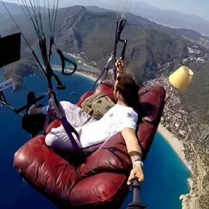 Турчин лета со параглајдер над морето, седнат на двосед