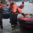 Woman dies in swollen river as floodwater breaches banks and defences