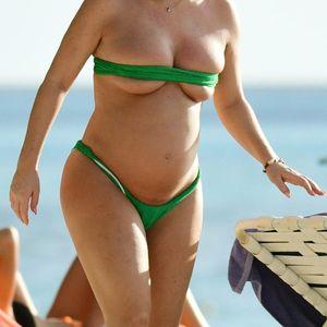 Pregnant Lauryn Goodman avoids tan lines on the beach in tiny green bikini in Barbados