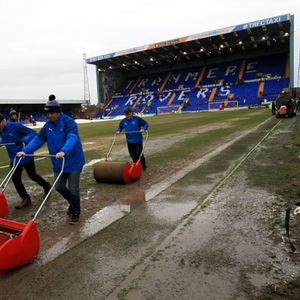 Groundsmen rush to shove standing water off Tranmere pitch as Man Utd warm up on muddy field