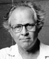 A black and white photograph of a man wearing glasses, and a white polo shirt