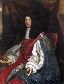 Seated man of thin build with chest-length curly black hair