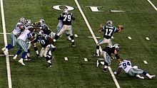 A quarterback is shown in the process of throwing a forward pass. His offensive linemen are in front of him.