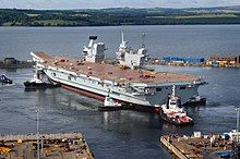 A Queen Elizabeth-class aircraft carrier docked in Scotland. This ship is one of two aircraft carriers, Portsmouth is its home port.
