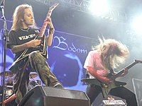 """A color photograph of two members of the group Children of Bodom standing on a stage with guitars, drums are visible in the background. Both electric guitarists have """"flying V"""" style guitars and they have long hair."""