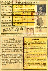An old document made of one sheet of paper showing two outlined boxes, one in the top half and one on the bottom. The top box has writing in Japanese with a translation and a small head shot of a woman with a thumbprint below it. There are several small square imprints in red ink from a stamp. The bottom box is split into two vertical halves, one in Japanese and the other in Indonesian.