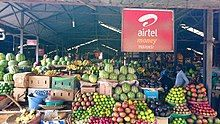 Interior photograph of the market, showing fruit available for sale as well as a hoarding advertising Airtel