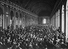 Photograph of the long Hall of Mirrors where an immense crowd is packed standing up around a group of seated individuals.