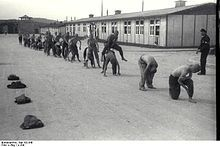 """A line of half-naked prisoners performing """"leap frog"""", under supervision of one of the Kapos. In the background the main gate to Mauthausen as well as two wooden barracks are visible."""