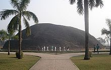 A very large hill behind two palm trees and a boulevard, where the Buddha is believed to have been cremated