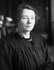 a black-and-white photograph of a young woman in a black smock