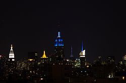 Upper floors of the Empire State Building lit in blue, amid other lit skyscrapers