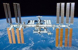 A forward view of the International Space Station with limb of the Earth in the background. In view are the station's eight paired maroon-coloured solar array wings, four on either side of the station, mounted to a central truss structure. Spaced along the truss are ten white radiators. Attached to the centre of the truss is a cluster of pressurised modules arranged in an elongated T shape. A set of solar arrays are mounted to the module at the aft end of the cluster.