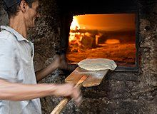 A man using a bread peel to slide a round disk of raw flatbread dough into a brick oven