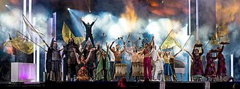 """Photograph of performance of """"Love Love Peace Peace"""" at the 2016 grand final: Petra Mede and Måns Zelmerlöw perform on stage surrounded by performers dressed in costumes of past Eurovision acts"""