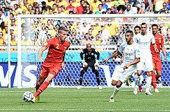 Belgian defender maneuvering around the Algerian goal