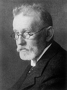 Portrait of an older, thin man with a beard wearing glasses and dressed in a suit and tie