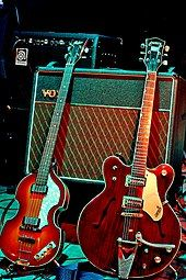 Two electric guitars, a light brown violin-shaped bass and a darker brown guitar resting against a Vox amplifier