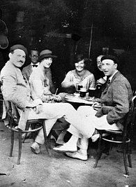 photograph of three men and two women sitting at a sidewalk table