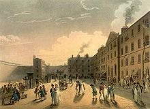Painting showing a yard inside a prison. The yard is surrounded on all sides by walls. Some people are walking around others are sitting at tables. In general, the people are dwarfed by the buildings and the color scheme is yellow and almond.