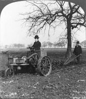 """A black-and-white photo of a man on an (1902 model) """"Ivel"""" tractor"""