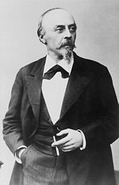 A middle-aged, balding man with a mustache and small beard, wearing a dark suit and holding a cigarette.