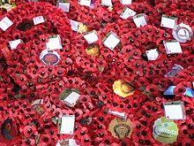 Several wreaths of artificial red poppies with black centres. The logo of various veterans and community groups are printed in the middle of each.