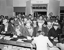 一大群工人挤在柜台前,两名女柜员正在俯身写字。有的工人将自己的证件照放在帽沿上戴着。