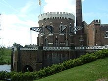 Round brick building of gothic architecture with steel beams protruding from the windows