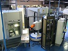 Large automated milling machines inside a big warehouse-style lab room
