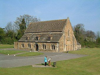 A tidy building like a large barn, of red brick with long sloping roofs, dormer windows and a low arched doorway.