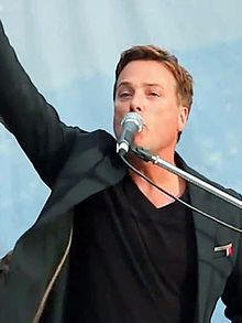 Michael W. Smith sings into the microphone with one hand in the air